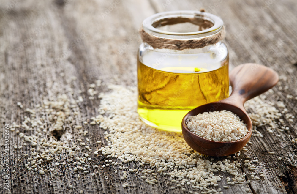 Fototapety, obrazy: Sesame oil with seeds on wooden background