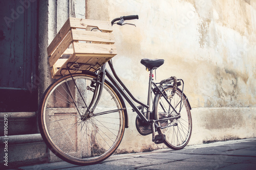 Photo Stands Bicycle vintage bicycle with wooden crate, bike leaning on a wall in italian street