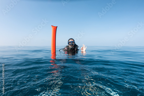 Weibliche Taucherin mit Taucherboje an der Wasseroberfläche gibt das OK Zeichen