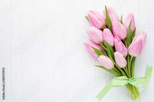 In de dag Tulp Fresh pink tulip flowers bouquet on shelf in front of wooden wall.