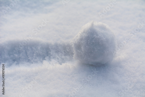 the snowball rolls over the snow; close up; selective focus