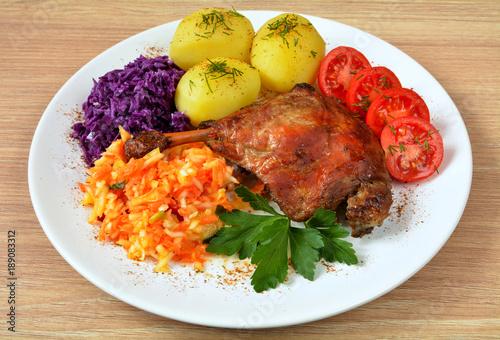 noga kaczki z ziemniakami, surówkami i pomidorem