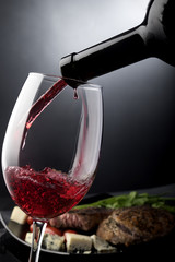 Closeup of red wine pouring into a glass in front of plate with cheese and meat