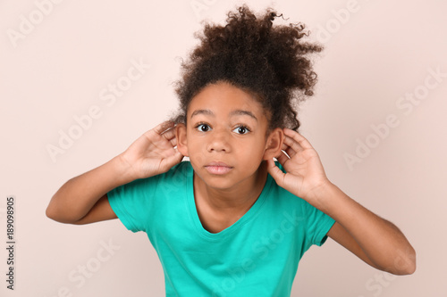 Little African-American girl with hearing problem on light background Wallpaper Mural