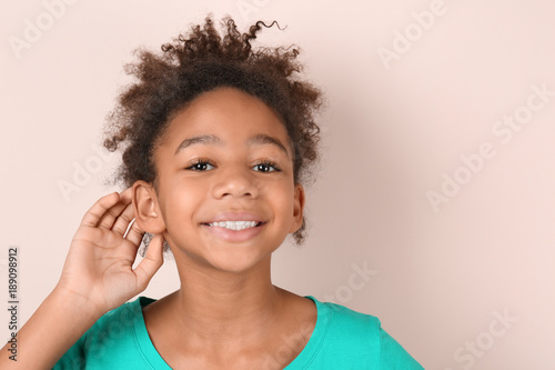 Photo Little African-American girl with hearing problem on light background