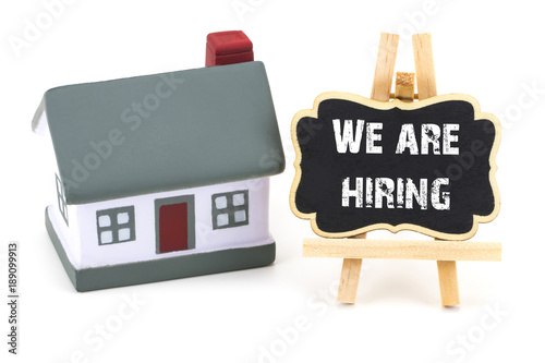 Fotografía  We are Hiring!  inscription on a blackboard and miniature model of house  on a