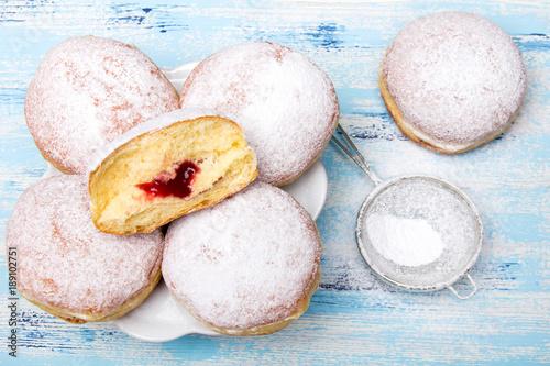 Fotografie, Obraz Tradycyjne polskie pączki z cukrem pudrem i dżemem na niebieskim drewnianym tle, podawane w tłusty Czwartek