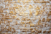Bricks Wall Painted In White And Gold. Background And Texture. Irregular Golden Bricks