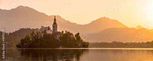 Fototapeta Island in lake Bled with orange Julian Alps sillhouette