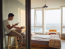 Lonely Man Chatting Smartphone And Drinking Coffee In His Room And Watching Sunset.