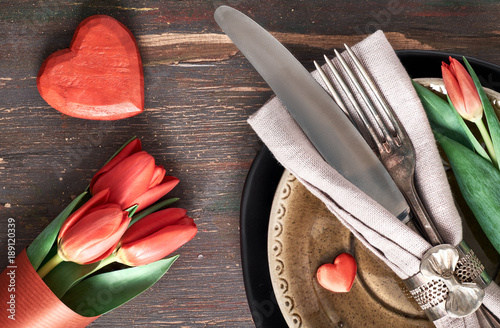 Springtime menu concept with fresh tulips and heart decoration on dark wood