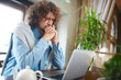 Troubled young businessman praying in front of laptop while reading online data during working day
