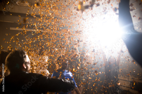 background image of golden confetti blast shooting over dancing