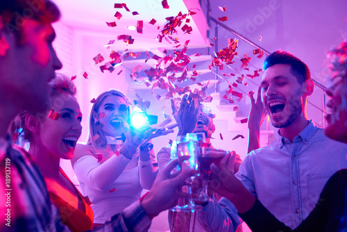 Group of happy festive people enjoying holiday celebration at private house party raising glasses under bursts of confetti