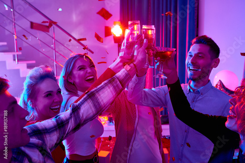 Group of happy festive people enjoying holiday celebration at private house party raising glasses and toasting under bursts of confetti