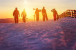 canvas print picture - Friends with ski and snowboards walking to sunset