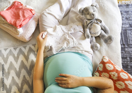 Photo  Pregnant woman is packing baby clothes