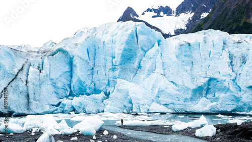 Man standing below massive glacier calving face in Alaska Canvas-taulu