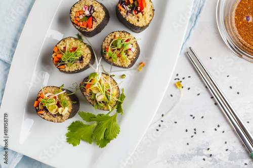 Vegan sushi rolls with quinoa, vegetables and soy-nut sauce on a white plate, light background. Top view. Vegan Healthy Food Concept.