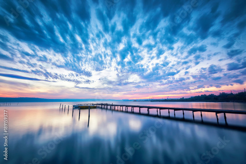 Amazing lake sunset / Magnificent long exposure lake sunset with boat and a wooden pier