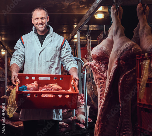 Photo The butcher in a meat freezer.