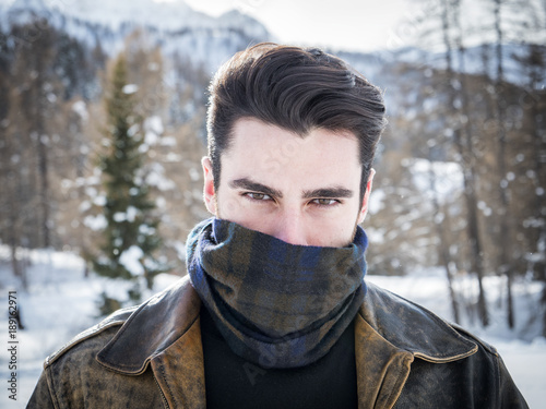Portrait of adult handsome man covering face with scarf looking provocatively at camera Fototapeta