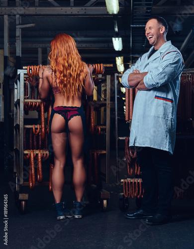 A chef and his female helper in a sausage storage. Fototapeta
