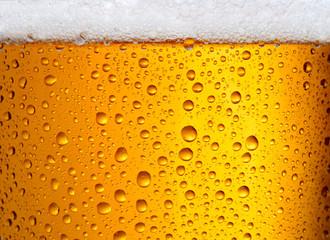 pogled izbliza na čašu piva s velikim kapljicama i pjenom