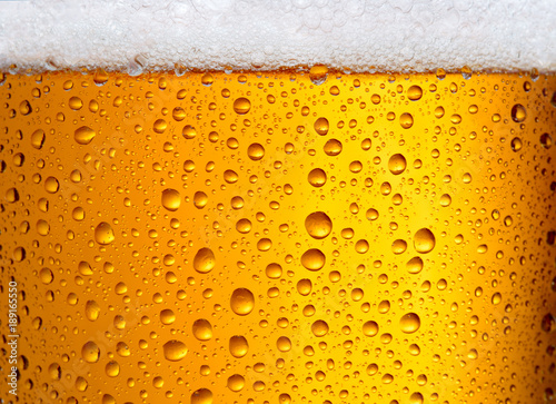 Canvas Print close-up view of glass of beer with big droplets and foam