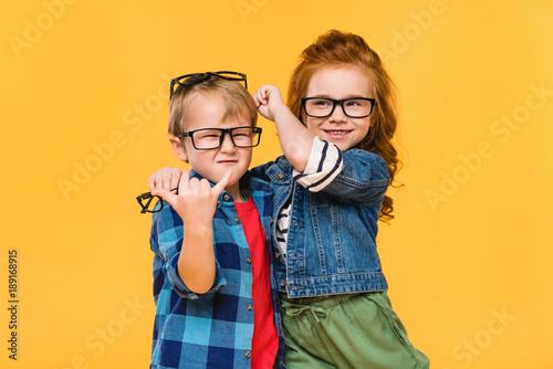 Obraz portrait of smiling kids in eyeglasses isolated on yellow - fototapety do salonu