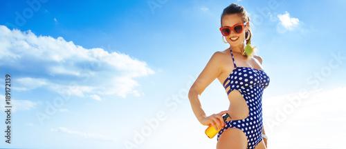 happy active woman in beachwear on beach applying suntan lotion Wallpaper Mural
