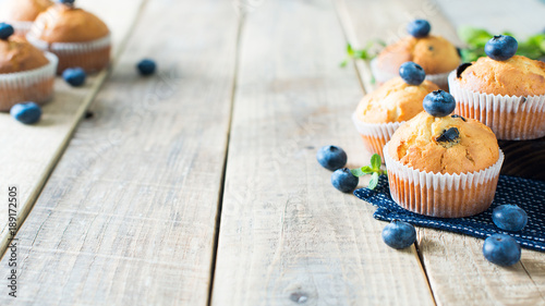 Obraz na plátně  Blueberries muffins or cupcakes with mint leaves on wooden texture