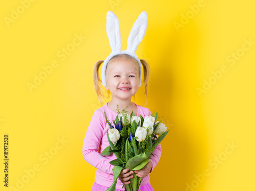 Pretty little girl easter bunny with spring flower on yellow background Canvas Print