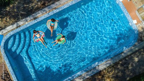Obraz na płótnie Widok z lotu ptaka z góry rodziny w basenie z góry, szczęśliwą matką i dziećmi pływać na pączkach pierścienia nadmuchiwane i baw się w wodzie na rodzinne wakacje