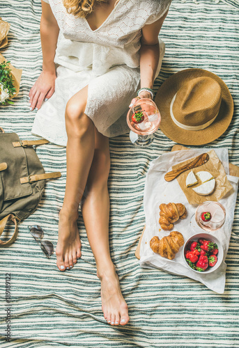 Keuken foto achterwand French style romantic picnic setting. Woman in dress with glass of wine, strawberries, croissants, brie cheese, sunglasses, straw hat, peony flowers on blanket, top view. Outdoor gathering concept