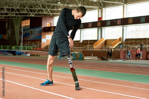Pinturas sobre lienzo  Portrait of young handicapped sportsman with artificial foot warming up before r