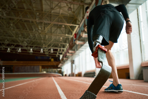 Tablou Canvas Motivational image of young amputee athlete on start position on running track i