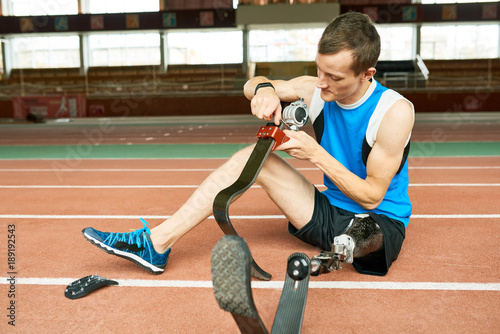 Photo  Full length portrait of young amputee sportsman sitting on floor in modern gym f