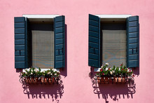 Italy, Venice, Burano Island. Traditional Colorful Walls And Windows With Green Shutters Of The Old Houses. Copy Space