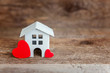 Miniature white toy house with red heart on a wooden table. Mortgage property insurance dream home concept