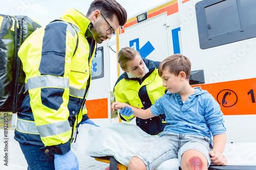 Photo Notarzt und Sanitäter kümmern sich um verletzten Jungen auf Transportliege
