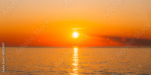 Foto op Plexiglas Zee zonsondergang Sun Is Setting On Horizon At Sunset Sunrise Over Sea Or Ocean.