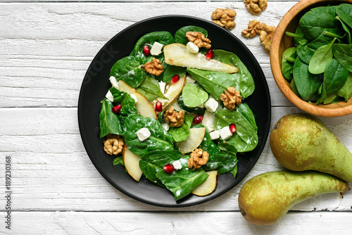 vitamin salad with spinach leaves, pear, nuts, pomegranate and feta cheese in black plate
