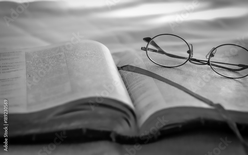 Reading Old Bible And Glasses Sitting Outdoors In Black White