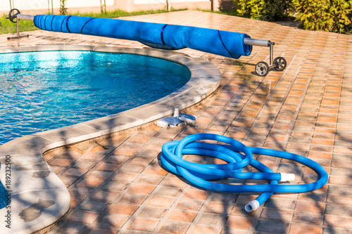 Fotografie, Obraz  Manual equipment for cleaning pool, brush, hose, swimming pool cover, Yesulskaya, Krasnodar, Russia