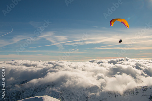 Fotografie, Obraz  Paragliding above mountain peaks and clouds during winter sunny snowy day
