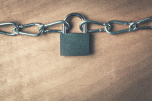 Padlock And Chains On A Wood Background.