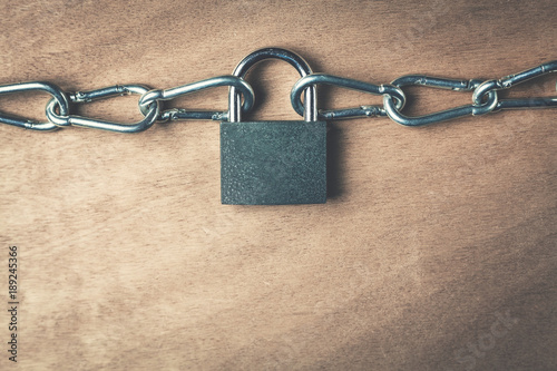 Photographie  Padlock and chains on a wood background.
