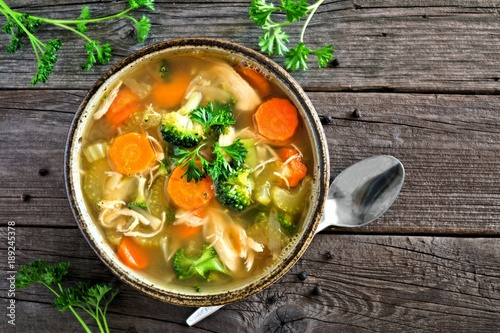 Homemade chicken vegetable soup, top view on an aged rustic wood background