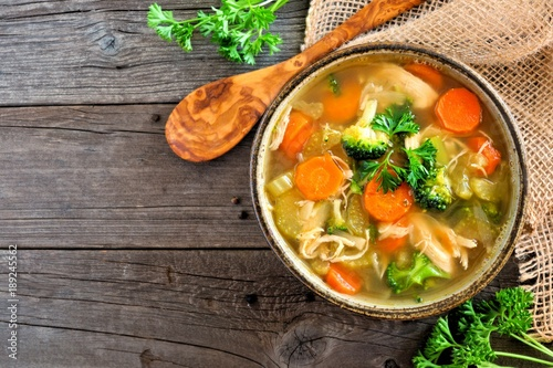 Fotografie, Tablou Homemade chicken vegetable soup, above view with copy space on a rustic wooden b